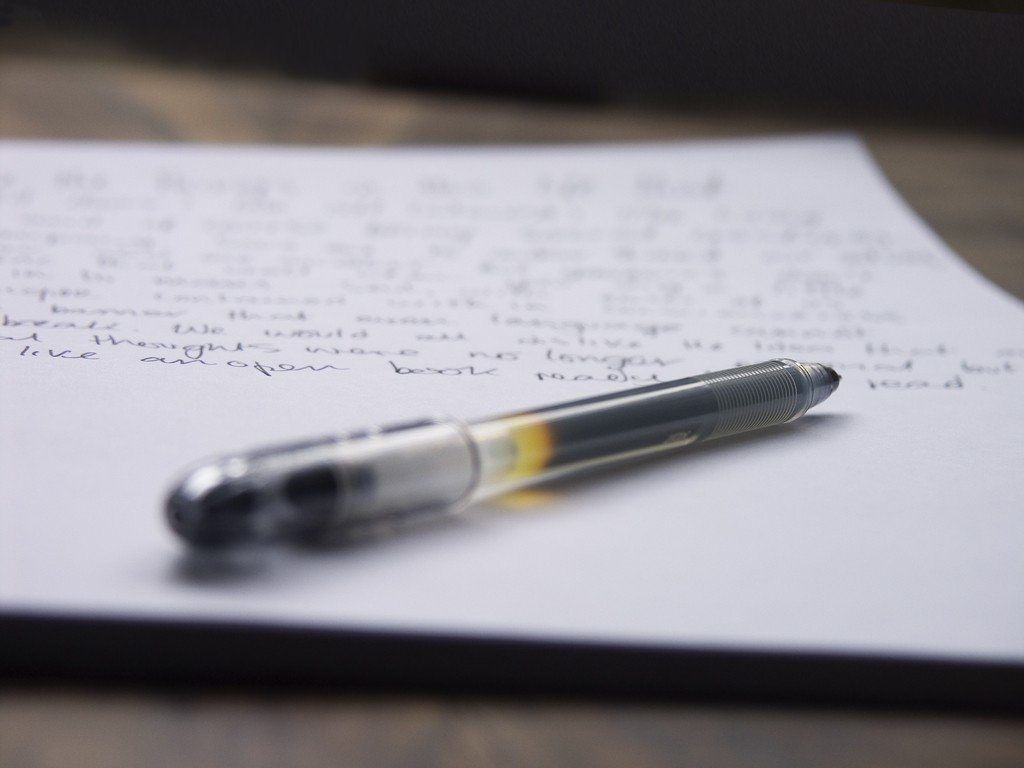 Image of a pen lying on paper which has writing on it