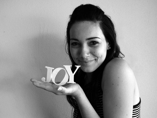Image of woman looking happy and holding word Joy