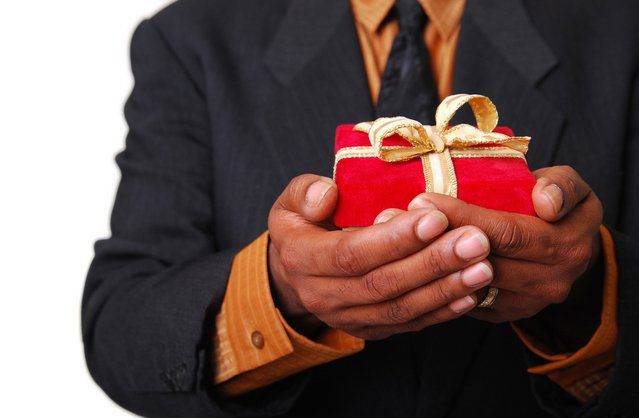Image of African-American male hands holding a red velvet box with gold ribbon.