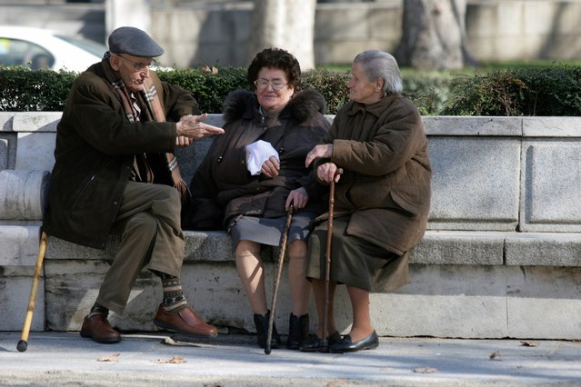 Image of 3 people sitting on a bench talking