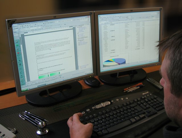 Image of man looking at computer screens