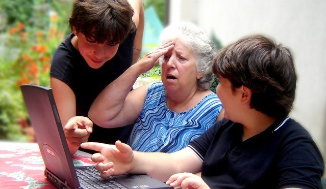 Image of children helping grandmother with laptop