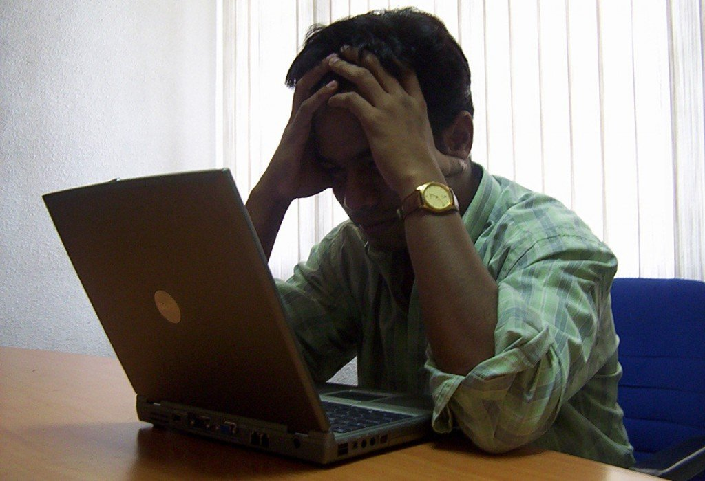 Image of man looking at a laptop
