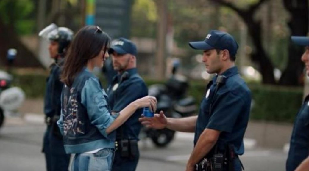 Image of Kendall Jenner in Pepsi ad giving a can to policeman